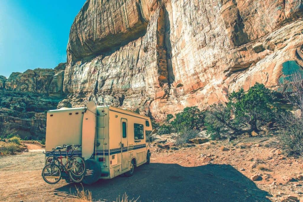 class c rv with mountain bikes mounted on the back parked by a rock face