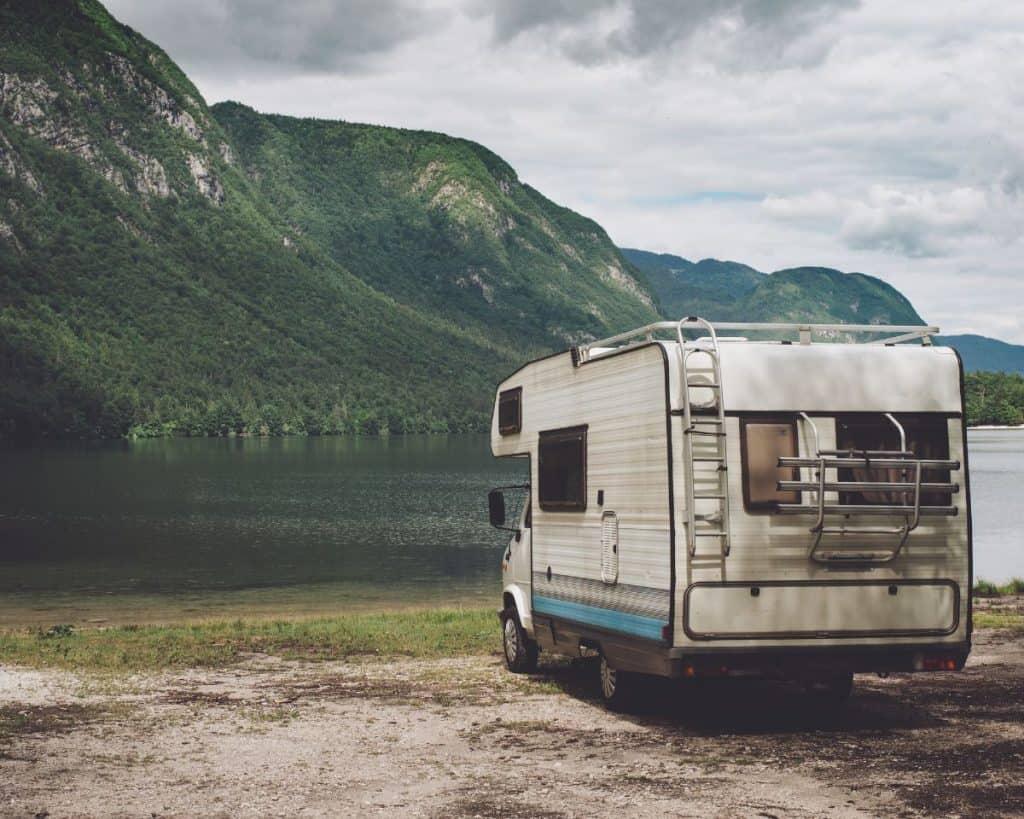 older class c rv parked by a lake shore