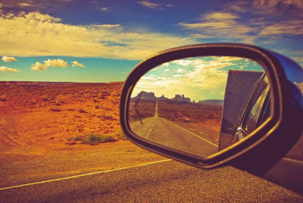 the road seen through the rearview mirror of a truck towing an rv