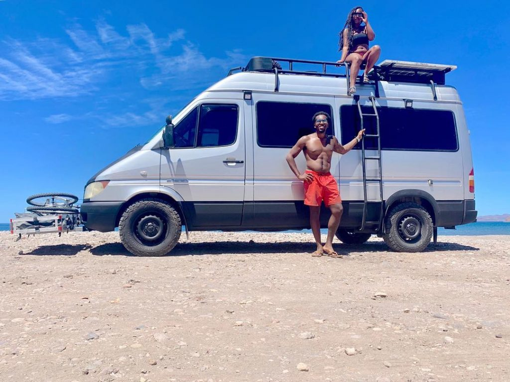 Van couple hangs out on the beach by their Sprinter van