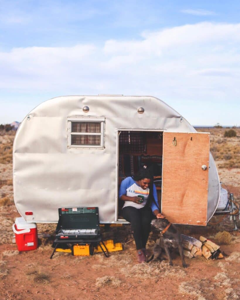 Woman sits in the doorway of her trailer in the desert
