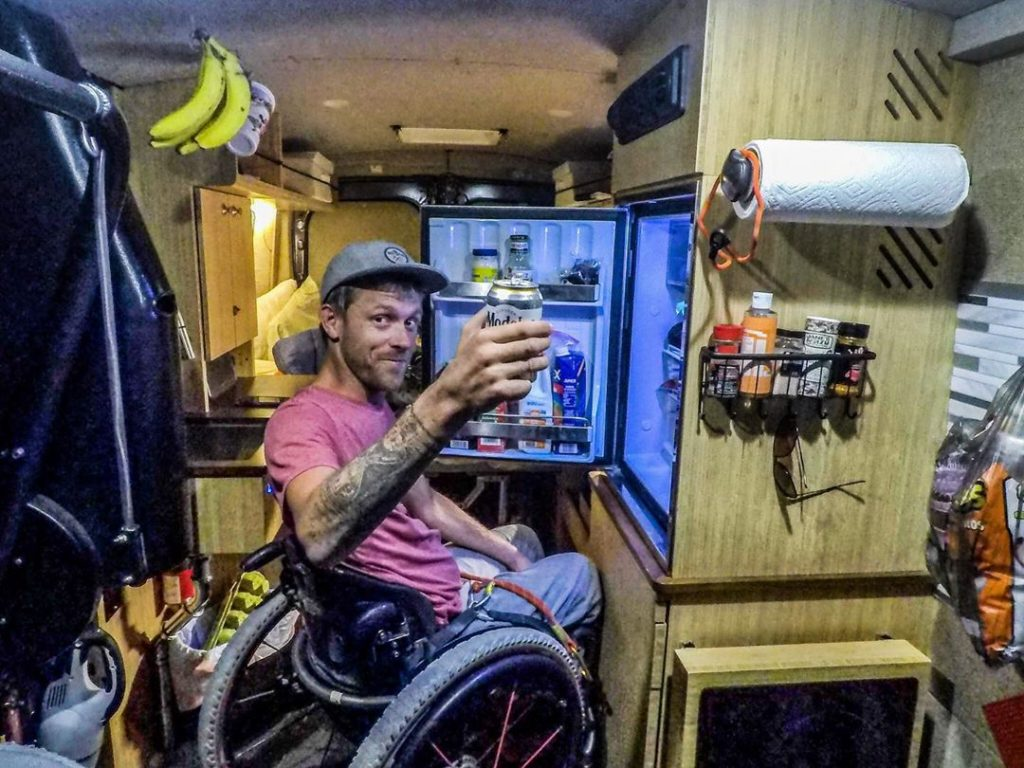 Man in wheelchair pulls a beer from his van fridge