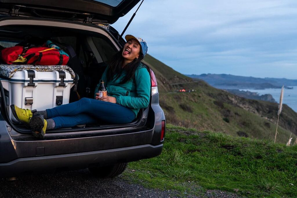 Woman hangs out in the back of her built out subaru
