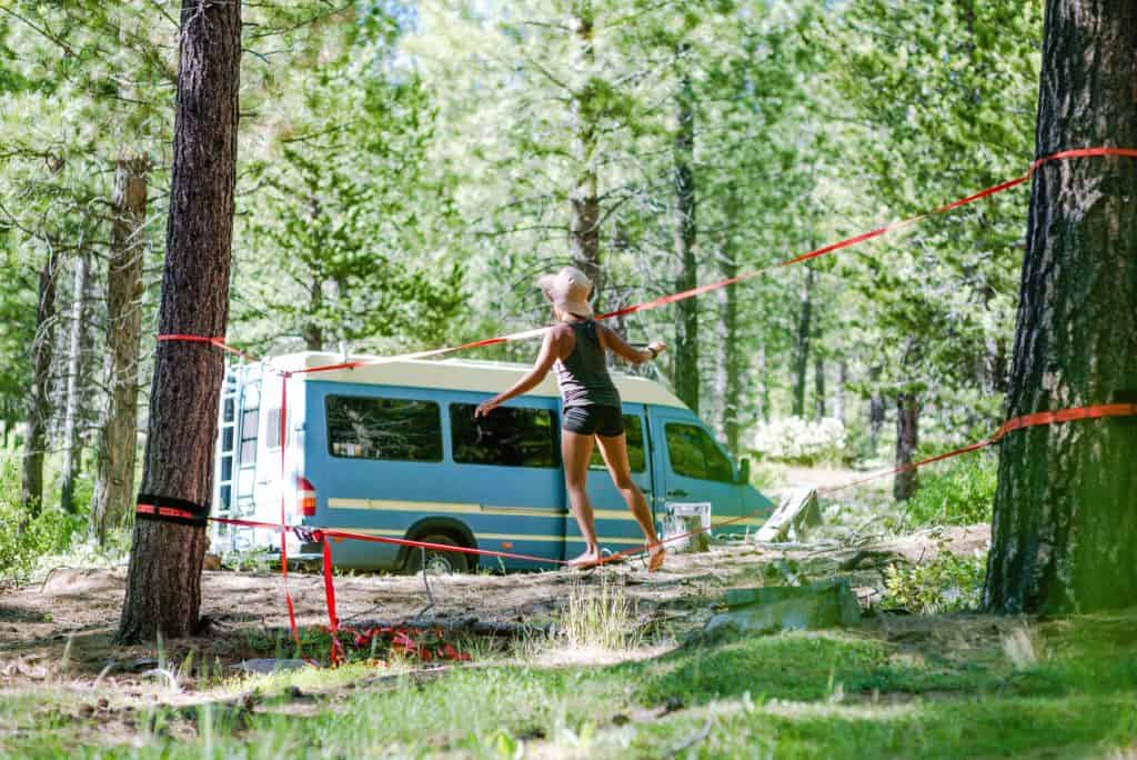 Nat walks across a slackline in the woods with the van in the background.