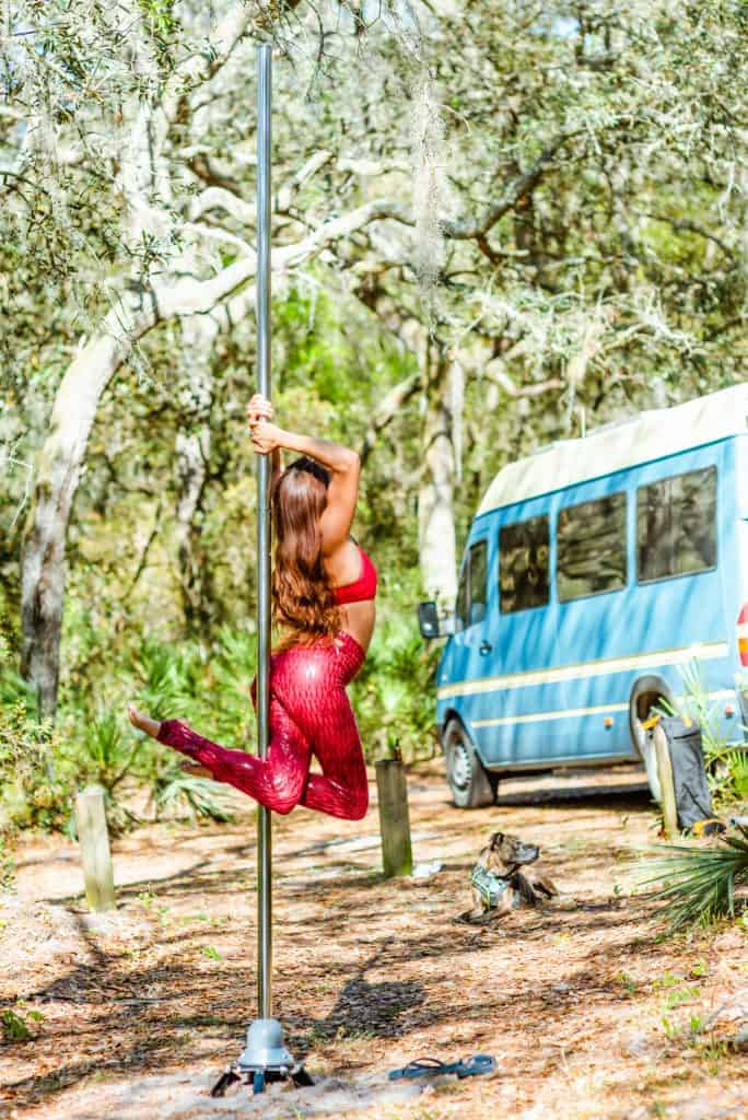 Abi practices a pole routine in the middle of the woods with the van in the background.