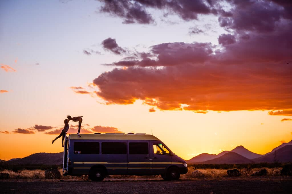 Nat stands on top of the van, bending over to kiss Abi who is climbing her way up the ladder. The sun is setting and there are Southwest mountains around them.