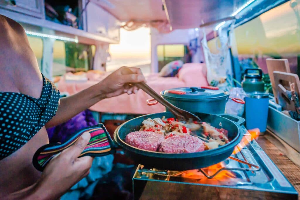 A close up of Nat cooking burgers and veggies in the van.