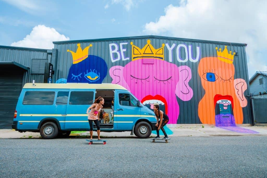 Abi & Nat skateboard in front of their van.