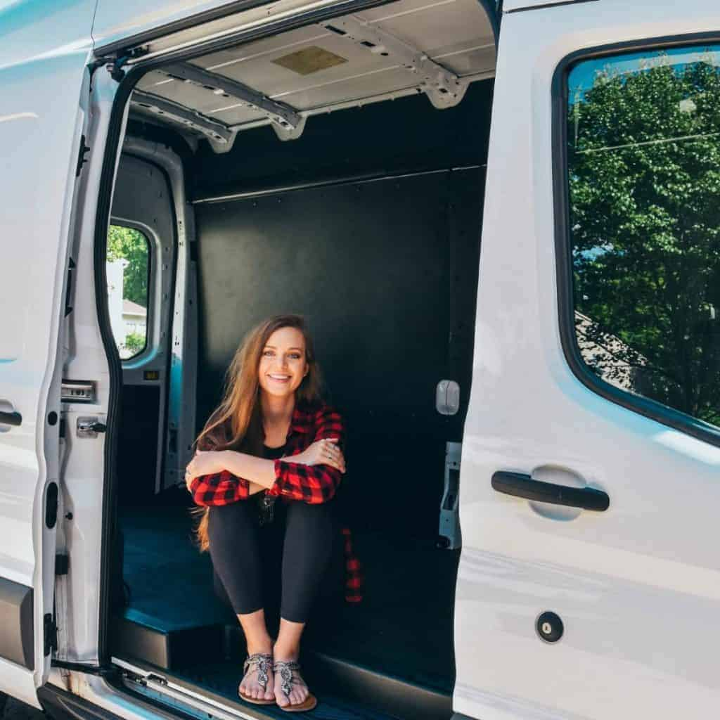 Sydney sits out the side door. Walls seem to be up in the van and a floor looks like it's installed too.