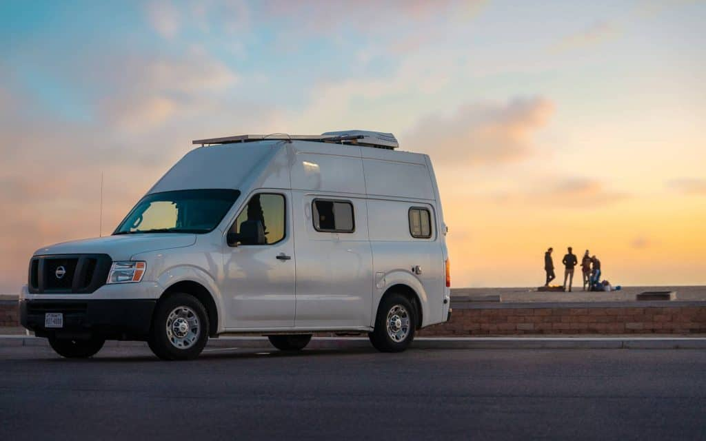 Exterior shot of the Nissan van with people hanging out in a distance.