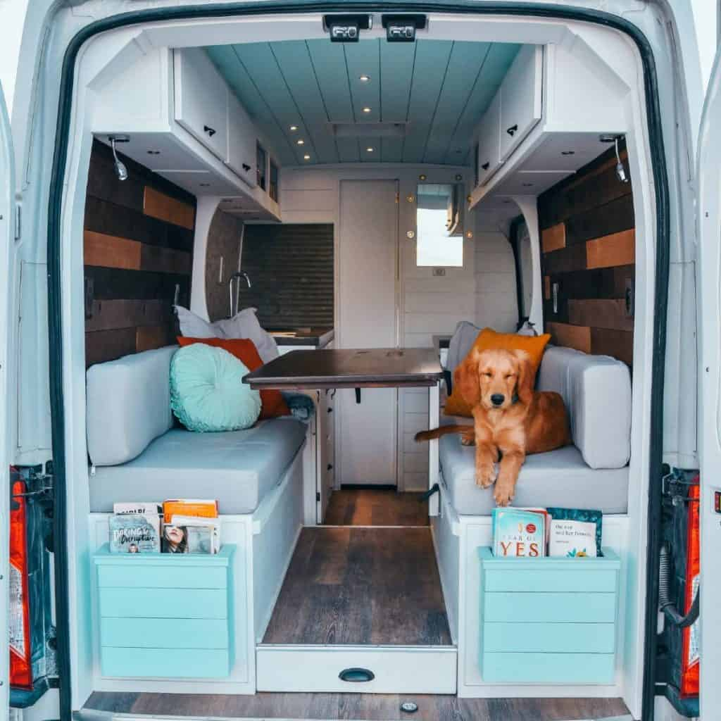 Ella sitting on the couch looking relaxed, the inside of the van is fully built out.