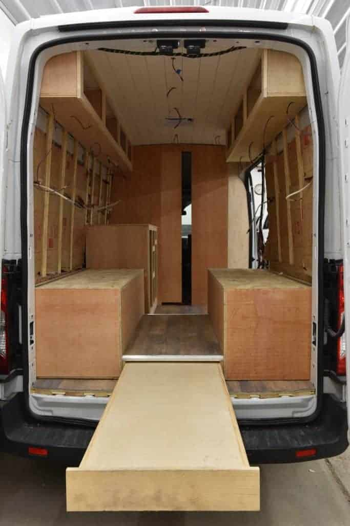 An interior shot of the van mid-build, filled with framed walls and the base of the couches.