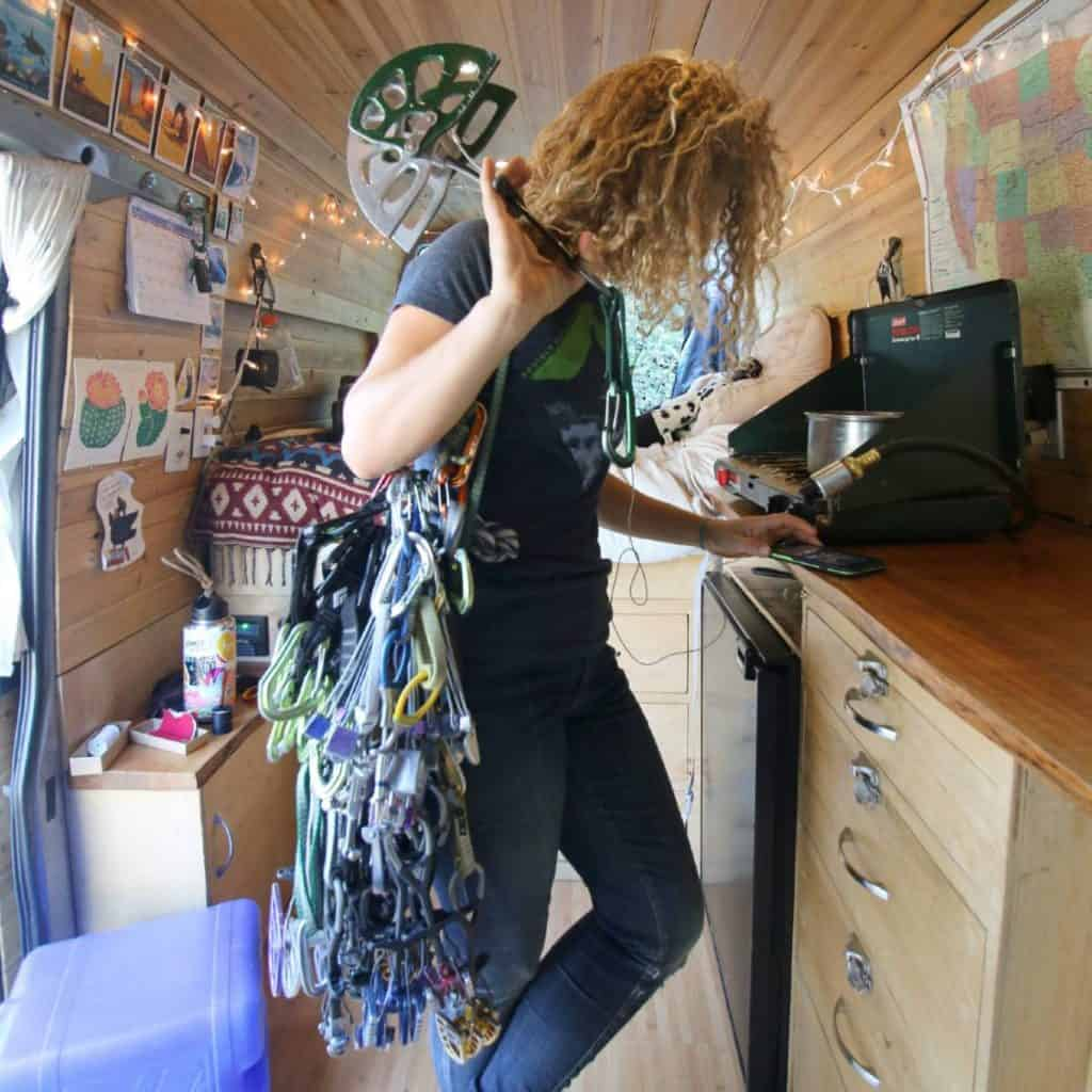 Kaya stands in the kitchen of her van holding cams and carabiners.