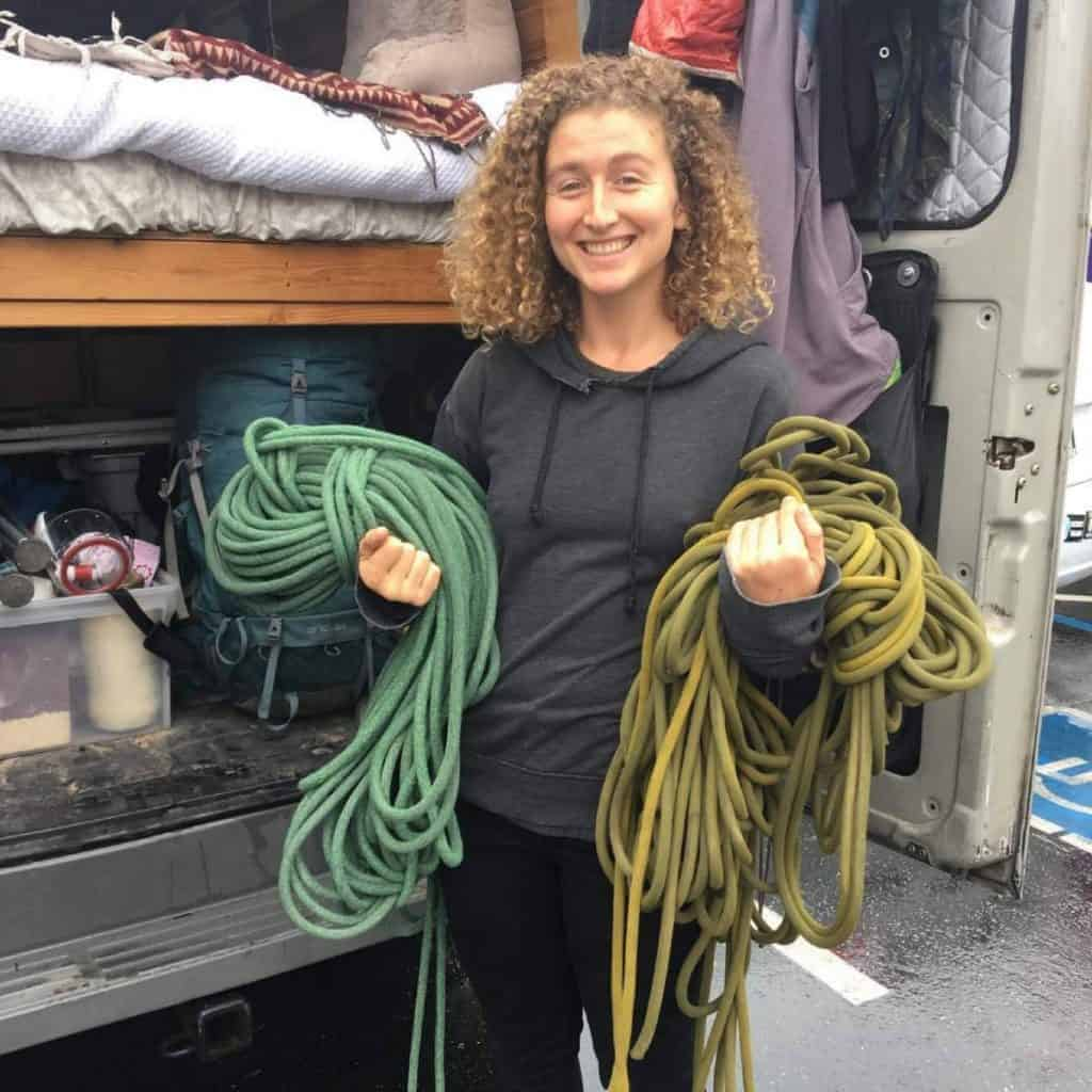 Kaya holds two bundles of ropes out the back of her van.