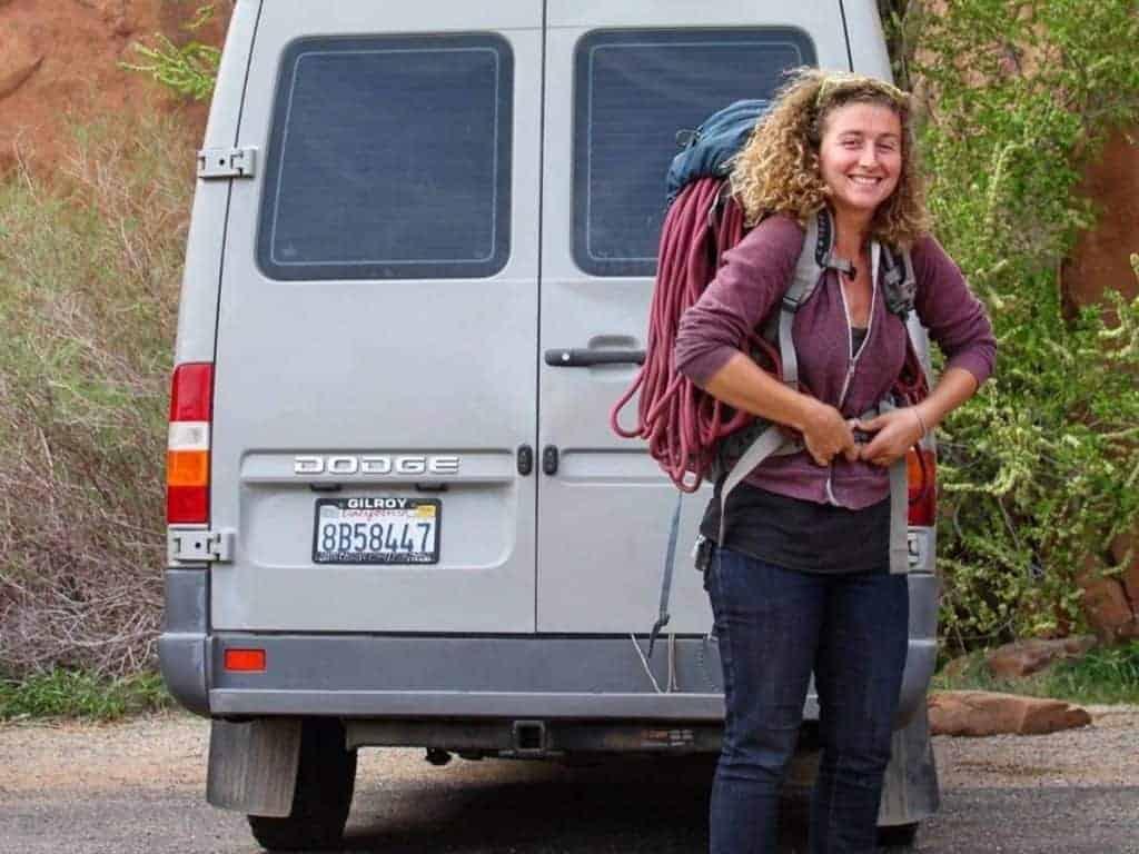 Kaya puts on a backpack behind her van.