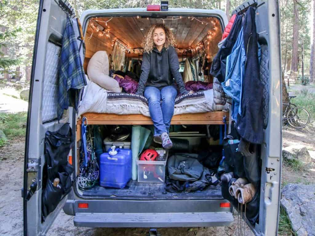 The back doors of Kaya's Sprinter are open. She sits on the bed facing out the back of her van. You are able to see her gear in the back of the van.