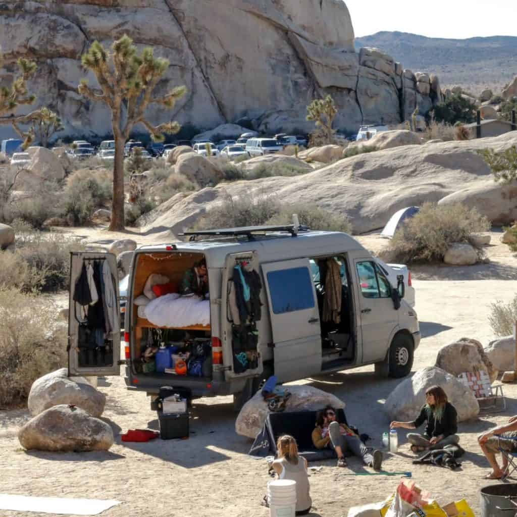 A van is parked surrounded by rocks and boulders with people hanging out outside of the van.