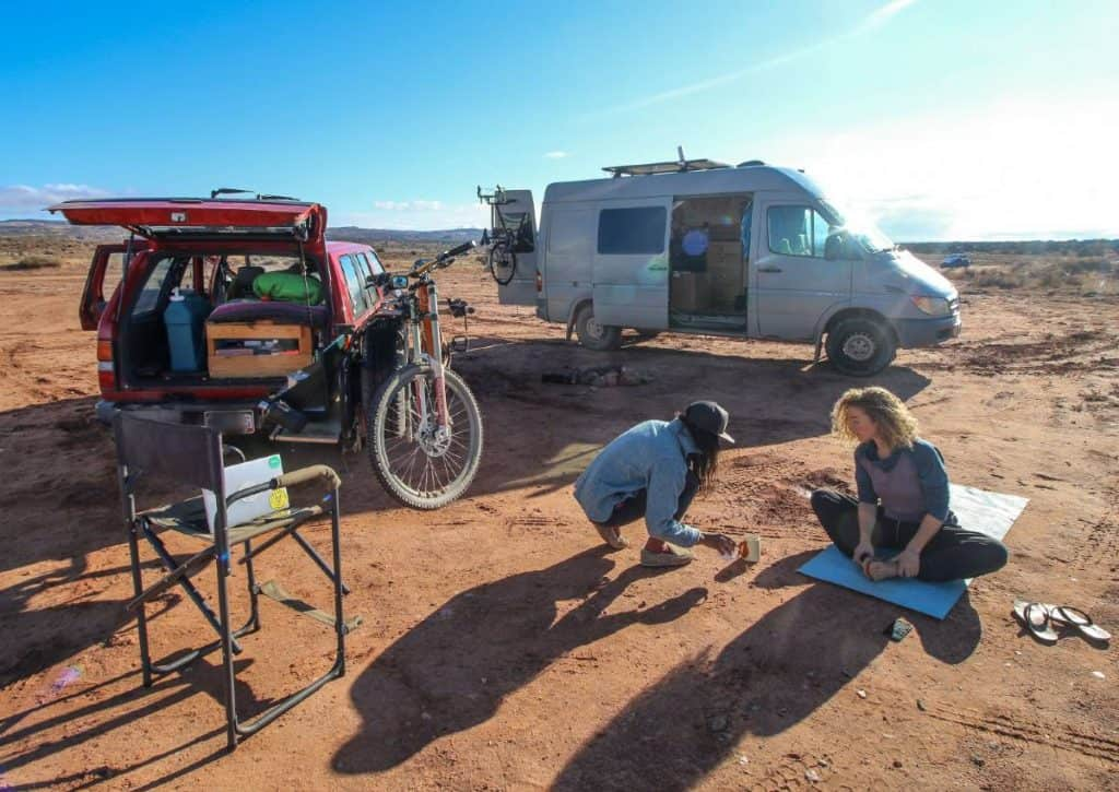 A van and an SUV are parked on flat dirt land. Two people hang out outside on the ground.