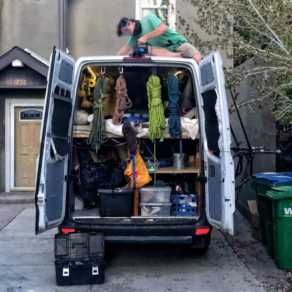 Someone is working on the roof of a van with the van's back doors are open. The back doors expose ropes and other rock climbing gear.