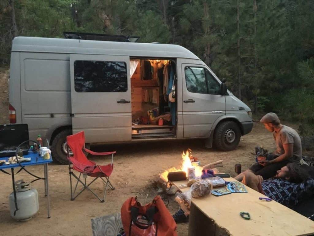 They have a campfire outside of the van.