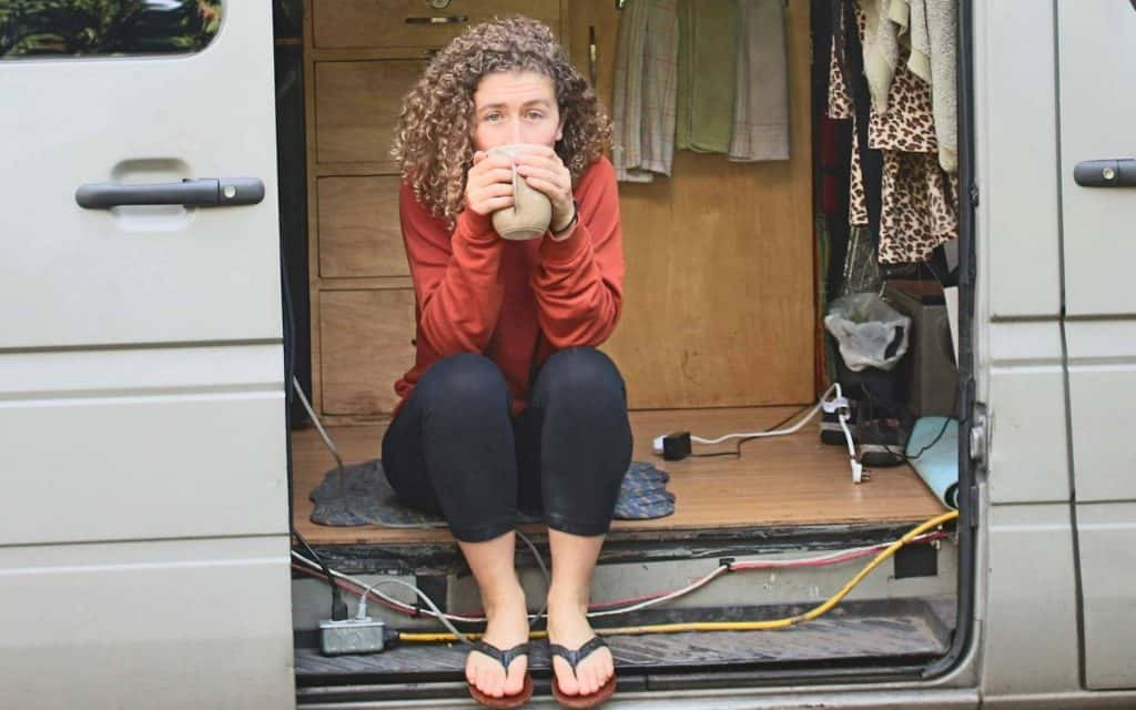 Kaya sits out her side door drinking coffee.