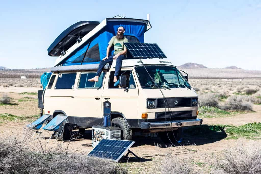 Dustin sits on the roof of the van next to the solar panel.