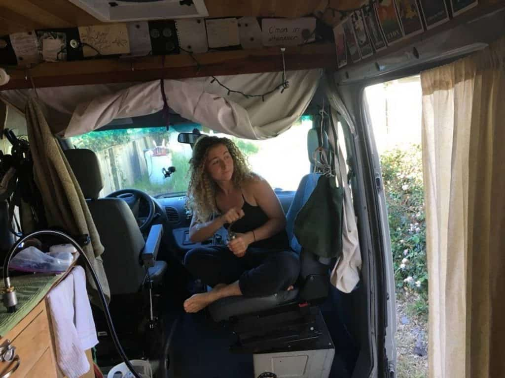 Kaya sits in her swiveled passenger seat, grinding coffee beans.