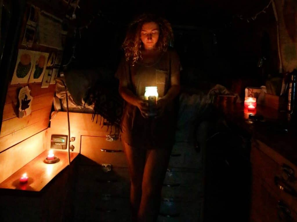 Kaya holds a candle, standing in the darkness of her van, surrounded by more candles.