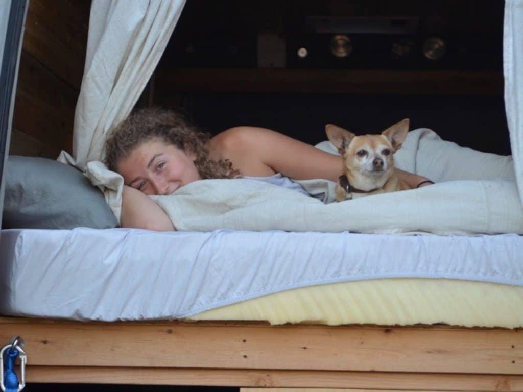Kaya lies in bed next to a dog.