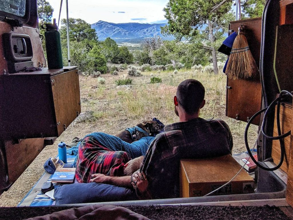 Jayme John and Nymeria cuddle outside of the van's side doors, under their awning, looking at a mountain range.