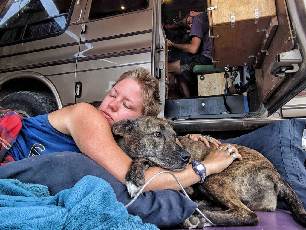 Jayme cuddles with her dog Nymeria out the van's side doors.