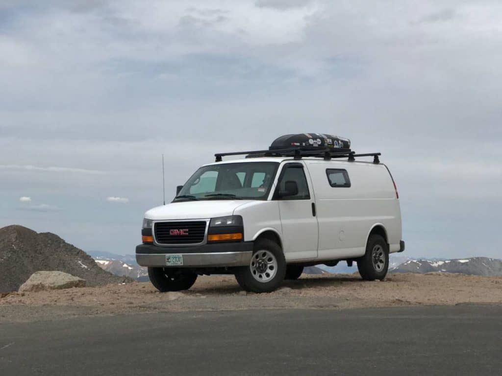 The van is parked on a ridge. You can see the ocean in the background.