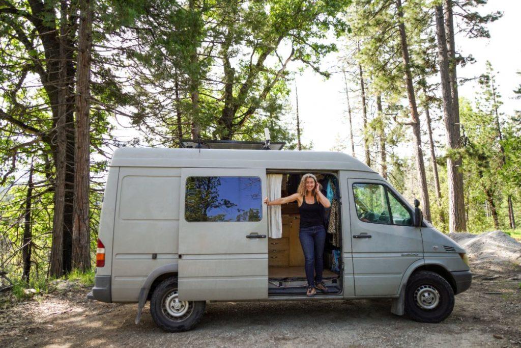 Kaya standing on the side door of her sprinter van