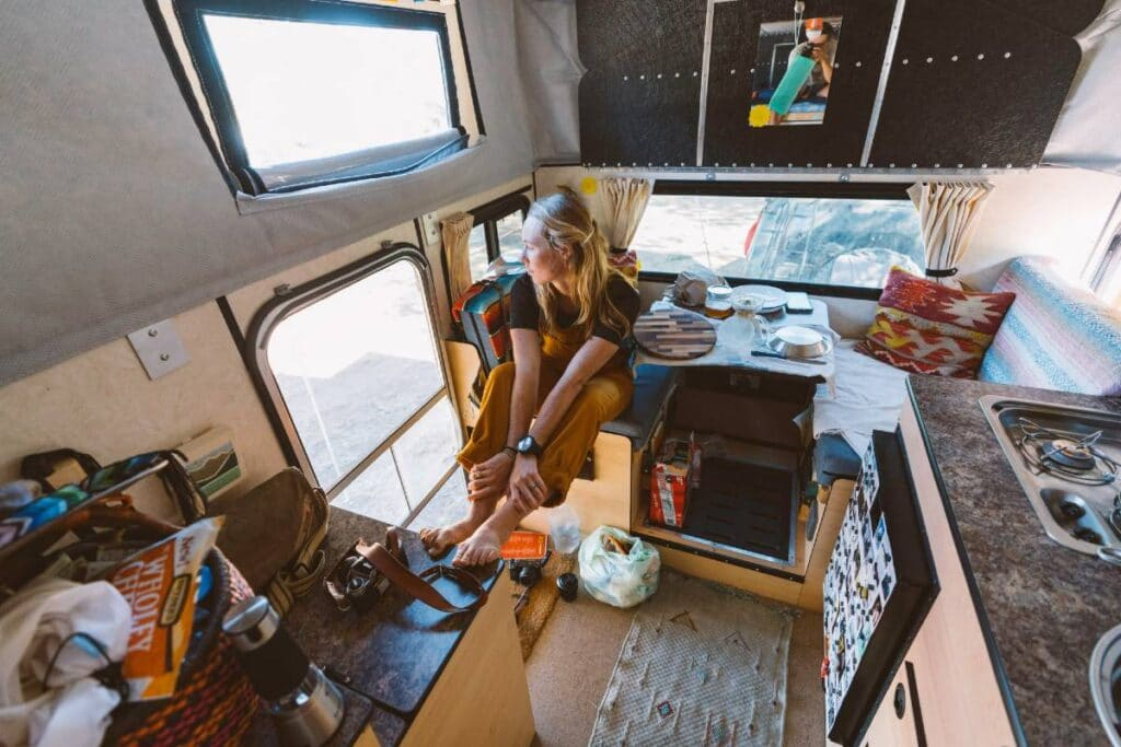 Interior of camper. Woman sits on dinette bench and looks out the open door