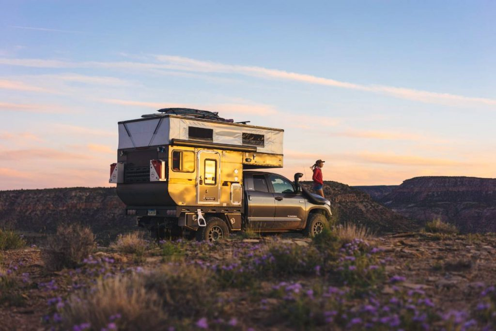 Toyota truck camper parked on the lip of a canyon, with woman standing on front bumper looking out