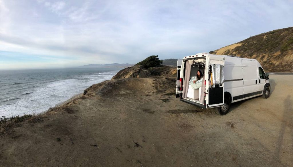 Dodge promaster parked at the beach with the back doors open