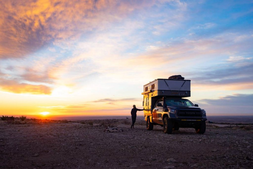 Toyota truck with camper parked by an amazing sunset