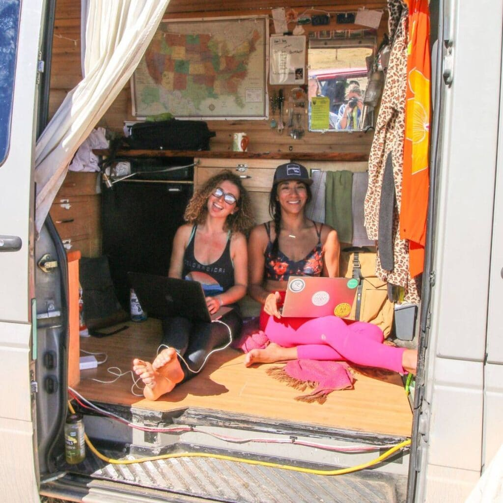 Two women hanging out in a Sprinter on their computers
