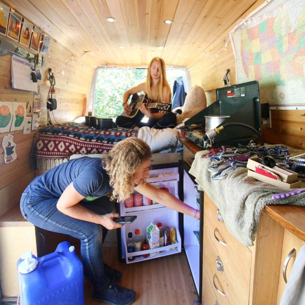 Two women inside a converted sprinter van. One sits on the bed playing the guitar, while the other grabs something out of the fridge