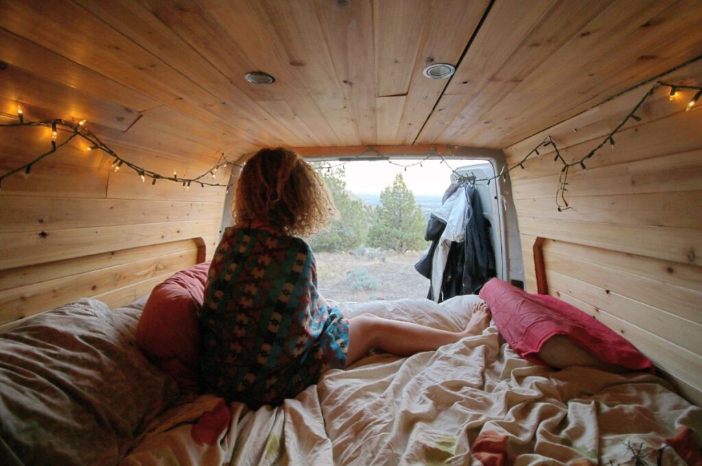 Woman sitting on bed inside Sprinter van looking out the back doors