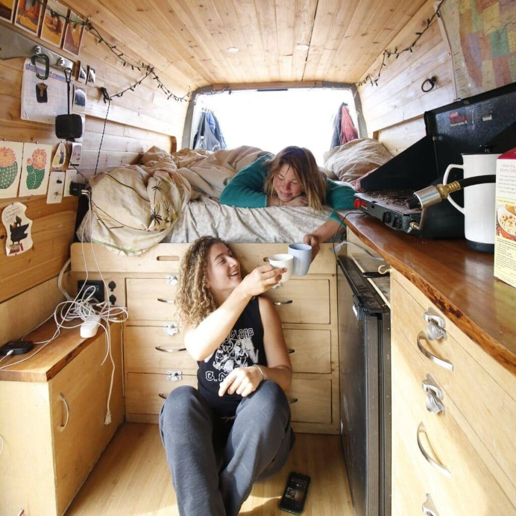 Two women sharing coffee inside a Sprinter van