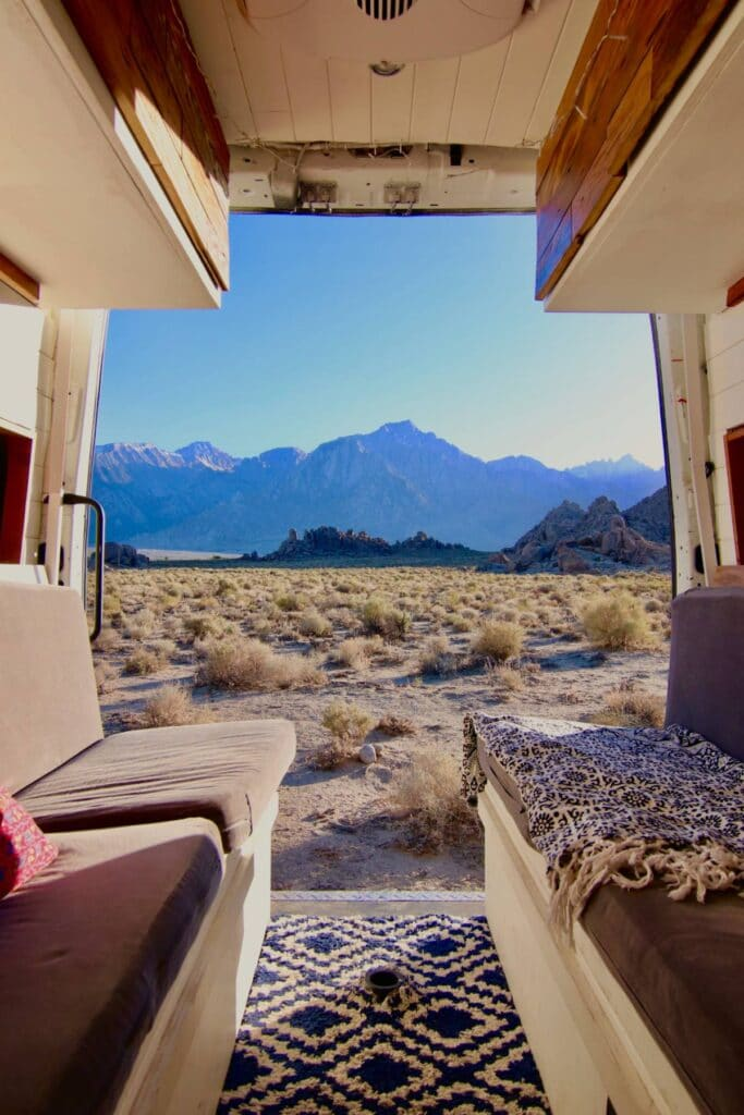 Looking out the back doors of a Nisaan NV2500 onto the mountainous desert