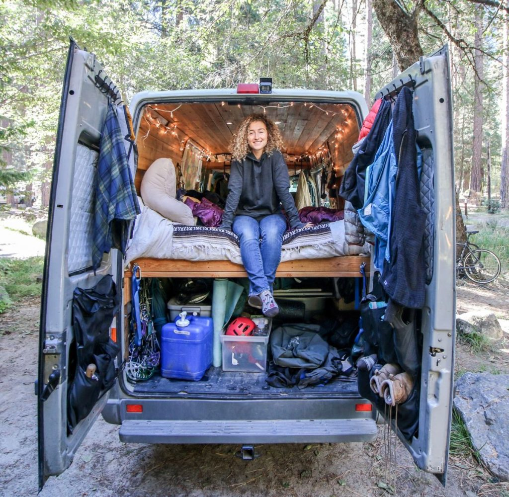 Showing inside the back door of a sprinter van, with a woman sitting on the bed
