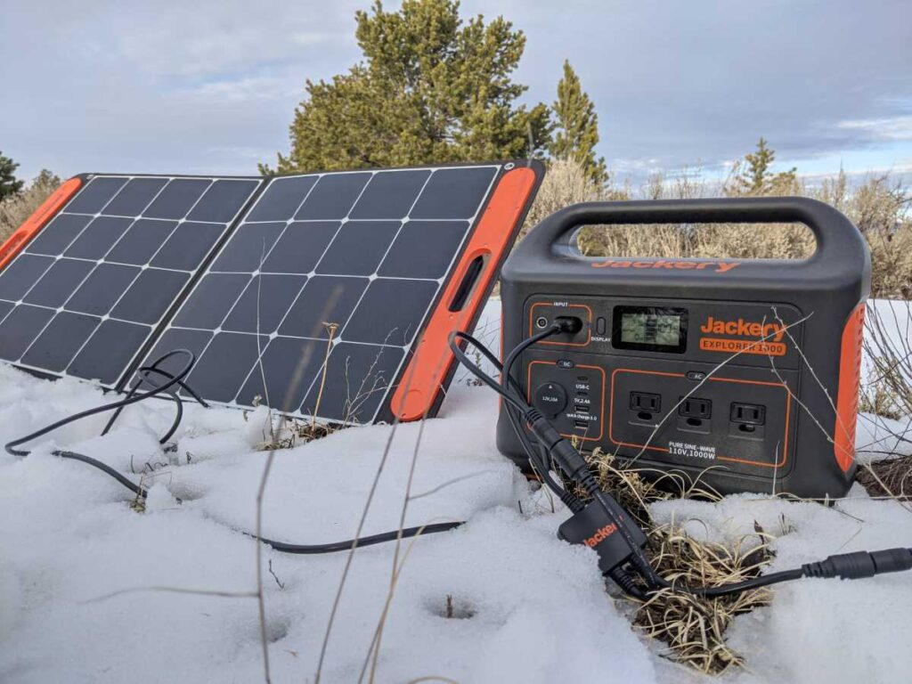 The Jackery 1000 on the snowy ground with a solar panel right next to it