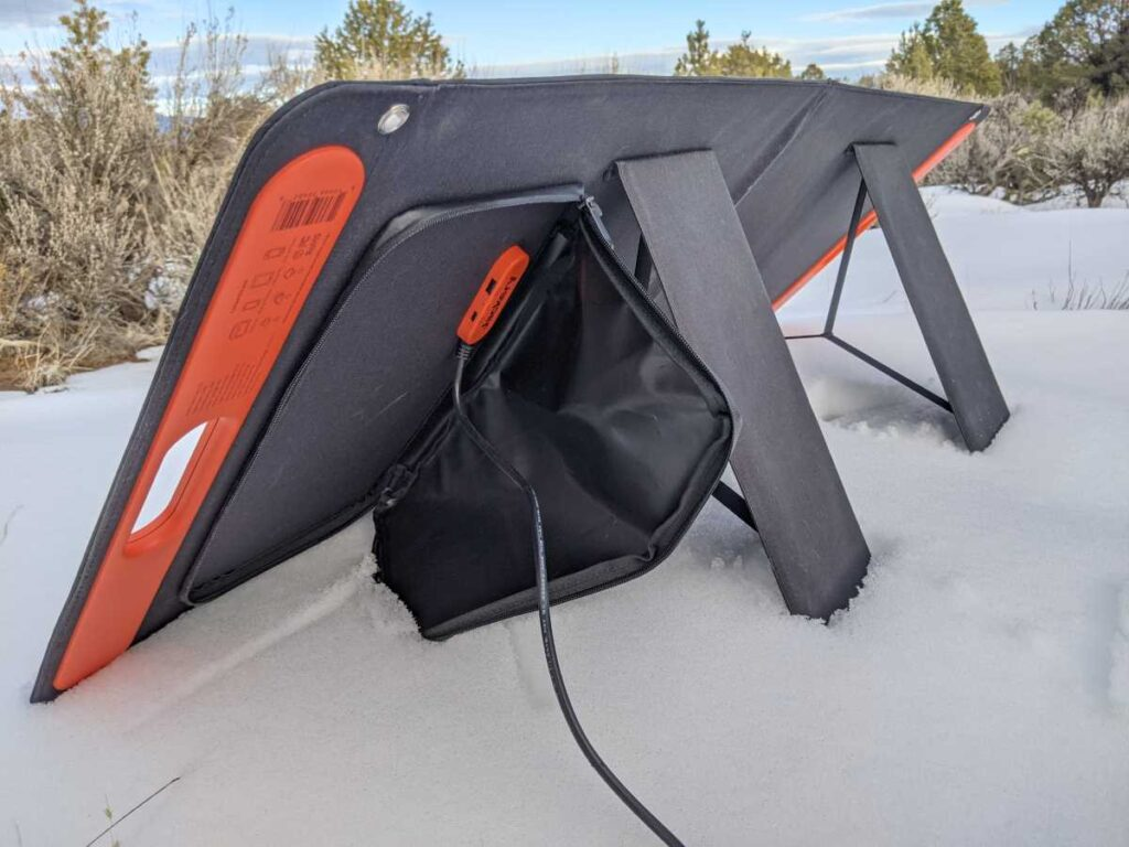 The SolarSaga 100W solar panel from behind, showing the kickstand, the cable pouch, and the USB ports
