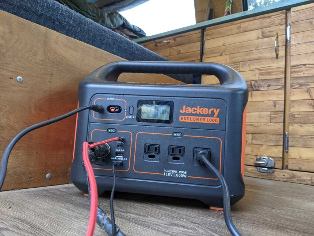 The Jackery 1000 sitting in the Gnomad Home van with a bunch of cables plugged into it
