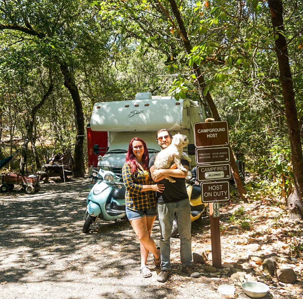 Couple standing by camp host sign