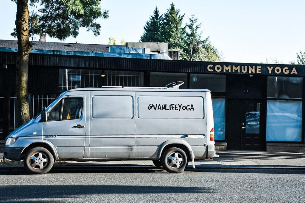 Sprinter van with #vanlifeyoga spray painted on the side