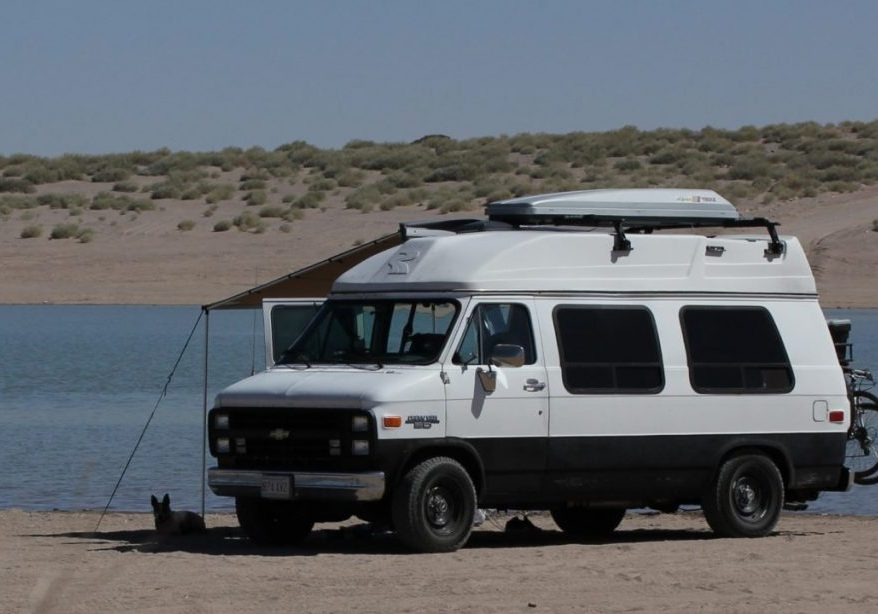 A white van decked out with adventure gear and a high top sits on a sandy beach.
