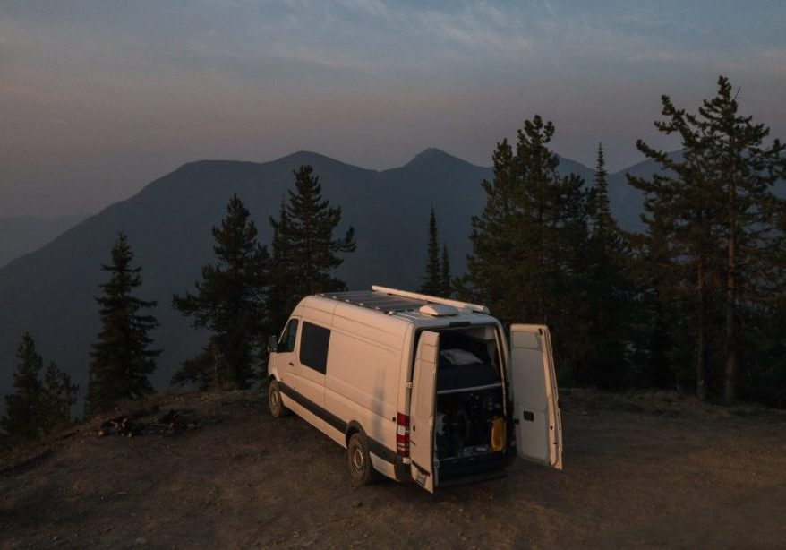 A white sprinter van sits at the edge of a cliff overlooking mountains with a dusk sort of haze to the background.